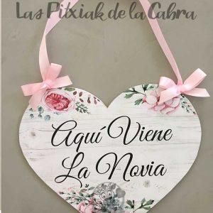 Cartel aquí viene la novia con forma de corazón y lazo rosa